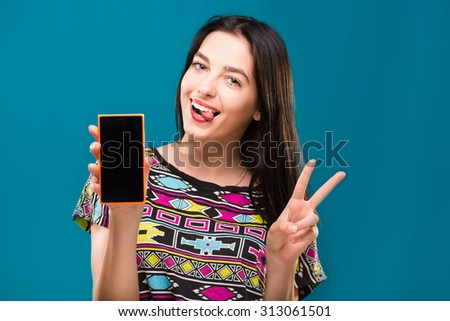 Cheerful young woman, with dark hair, wearing in colorful shirt, holding smart phone in her hand, on blue background, in studio, waist up - stock photo