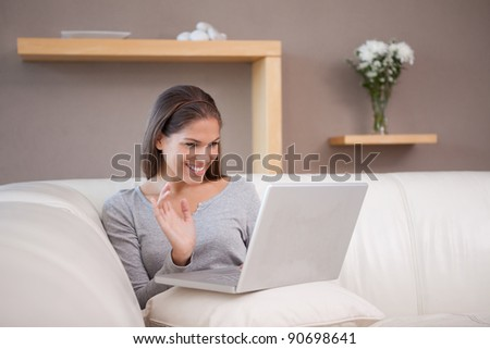Cheerful young woman with her notebook on the sofa