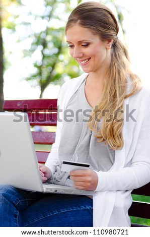 cheerful young woman with laptop and credit card sitting in a park - stock photo