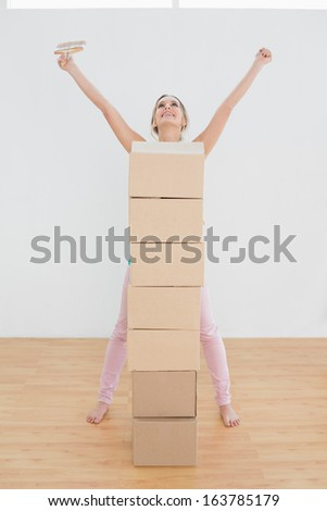 Cheerful young woman with stack of boxes and paintbrush raising hands in a new house
