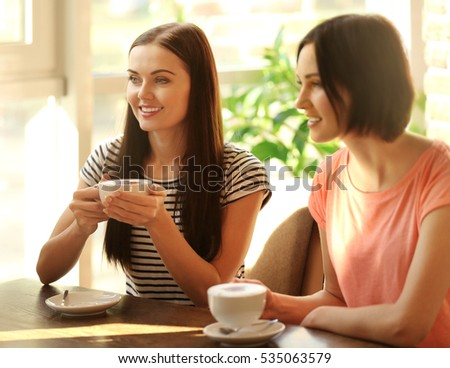 Cheerful young women drinking coffee in cafe on sunny day