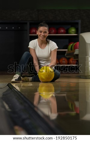 Cheerful Young Women Holding Bowling Ball