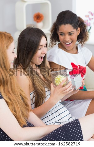 Cheerful young women surprising friend with a gift on sofa at home - stock photo