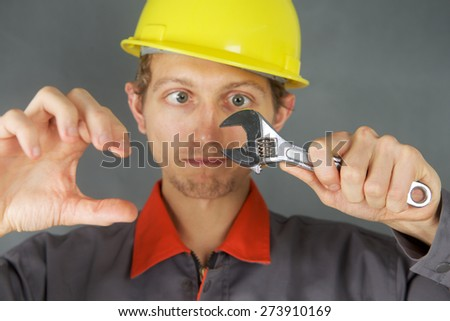 Cheerful young worker in overalls and a helmet with adjustable wrench in hand - stock photo