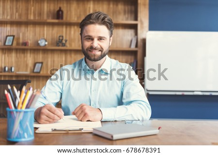 Cheerful youthful bearded guy performing formal task in office