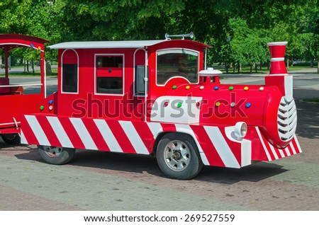 Cheerfully painted children's train for walks in the amusement park. - stock photo