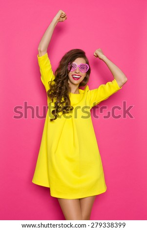 Cheering. Beautiful young woman in yellow mini dress and pink heart shaped sunglasses posing with arms raised. Three quarter length studio shot on pink background. - stock photo