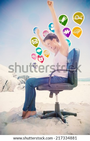 Cheering brunette using laptop on the beach sitting on swivel chair with colourful computer applications - stock photo