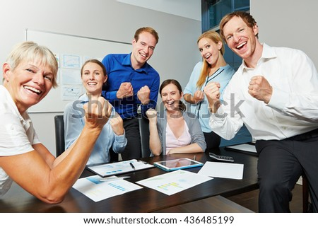 Cheering business people motivating with clenched fists in the office