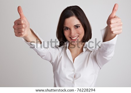 Cheering business woman holds both her thumbs up - stock photo