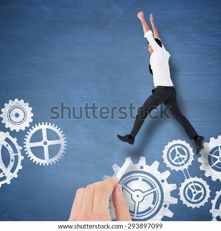Cheering businessman against blue chalkboard - stock photo