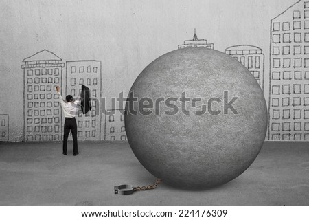cheering businessman free from concrete ball shackle with doodles wall - stock photo