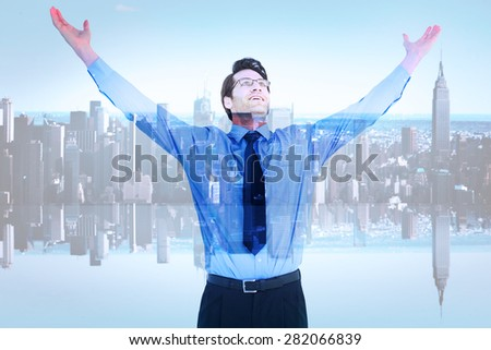 Cheering businessman with his arms raised up against mirror image of city skyline - stock photo