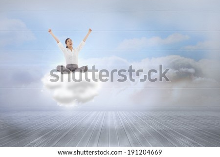 Cheering businesswoman sitting cross legged against clouds in a room - stock photo