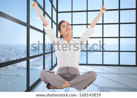 Cheering businesswoman sitting cross legged against room with large window showing city - stock photo