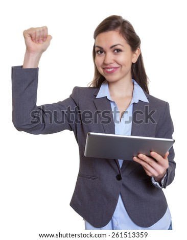 Cheering businesswoman with brown hair and tablet computer - stock photo