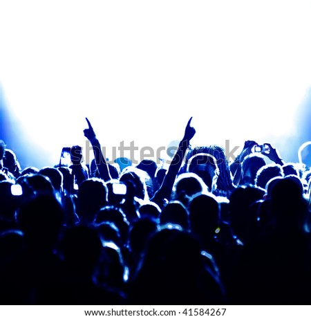 cheering crowd at concert in front of bright blue stage lights - stock photo