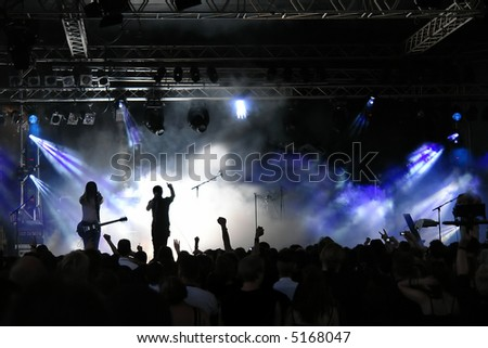 Cheering crowd at concert, musicians on the stage - stock photo