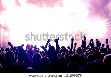 cheering crowd in front of bright purple stage lights