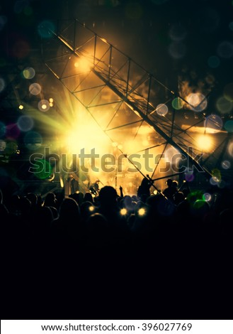 Cheering crowd in front of bright yellow stage lights. Nightlife in rock style - silhouettes of fun peoples on a music concert. Concept of vertical poster with place for your text on black background. - stock photo
