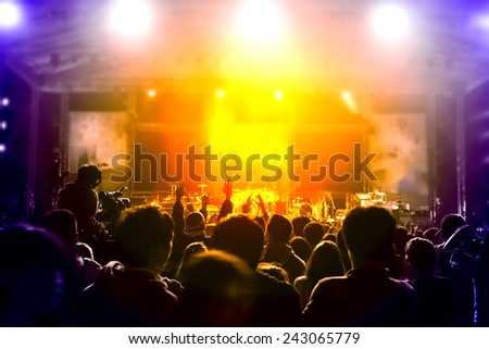 cheering fans put hands up during a live concert ,visible noise due high ISO, soft focus, slight motion blur  - stock photo