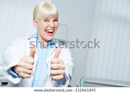 Cheering female dentist holding her thumbs up and congratulating