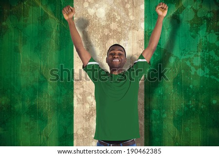 Cheering football fan in green jersey against nigeria flag in grunge effect - stock photo