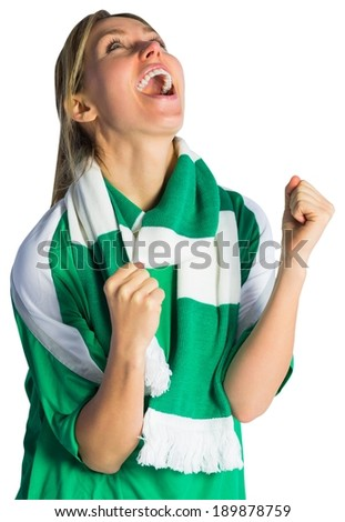 Cheering football fan in green jersey on white background - stock photo