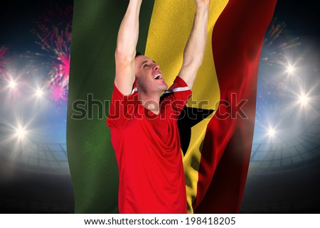Cheering football fan in red against fireworks exploding over football stadium and ghana flag - stock photo
