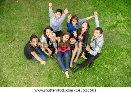 cheering group of friends holding hands up outdoors - stock photo
