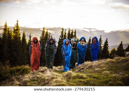 cheering group of hikers jumping in sleeping bags outdoors in mountains during the sunset - stock photo