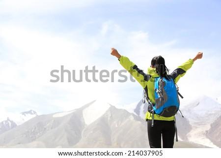cheering hiking woman open arms on mountain peak of tibet,china  - stock photo