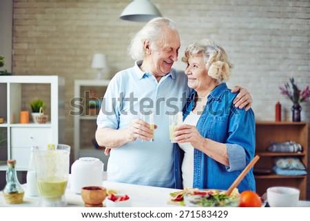 Cheering seniors with glasses of fresh smoothie - stock photo