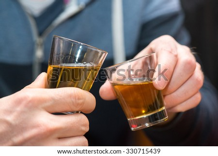 cheering with a glass of brown alcohol - stock photo