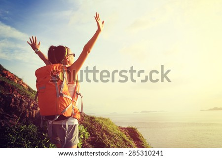 cheering woman backpacker on  seaside mountain  enjoy the view - stock photo