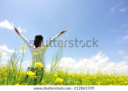 cheering woman open arms at cole flower field - stock photo