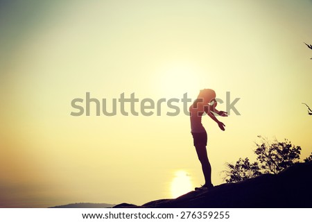 cheering woman open arms at sunset mountain peak - stock photo