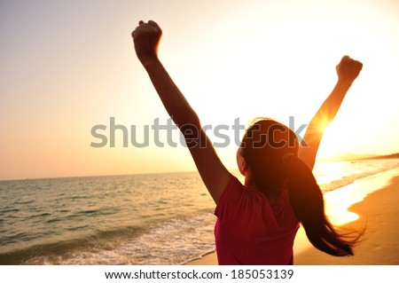 cheering woman open arms at sunset seaside beach  - stock photo