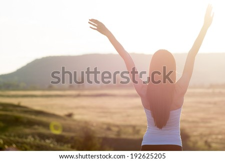 cheering woman open arms to sunrise - stock photo