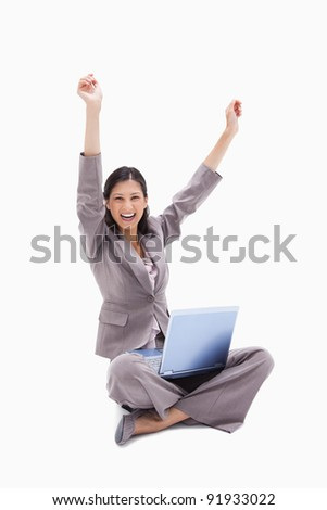 Cheering woman sitting with laptop against a white background