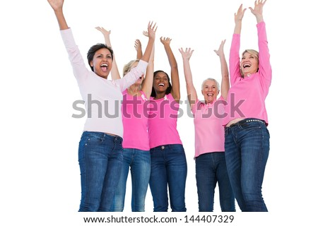 Cheering women wearing breast cancer ribbons on white background - stock photo