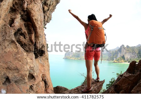 cheering young asian woman hiker open arms on seaside mountain peak - stock photo