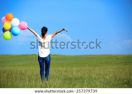 cheering young asian woman on green grassland with colored balloons  - stock photo