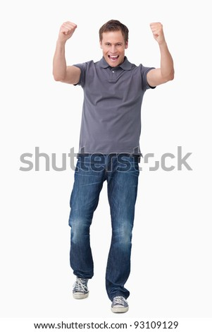 Cheering young man against a white background - stock photo