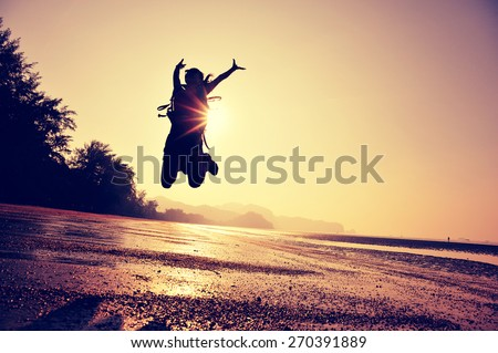cheering young woman hiker jumping on  sunrise beach  - stock photo