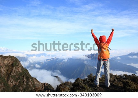 cheering young woman hiker open arms at mountain peak - stock photo