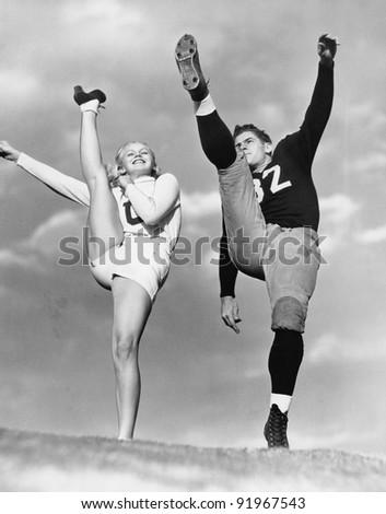 Cheerleader and football player kicking into the air - stock photo