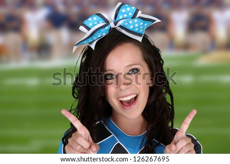 Cheerleader with uniform on at a football game - stock photo