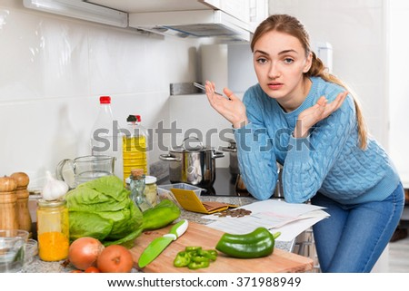 Cheerless displeased girl reading banking documents in home kitchen - stock photo