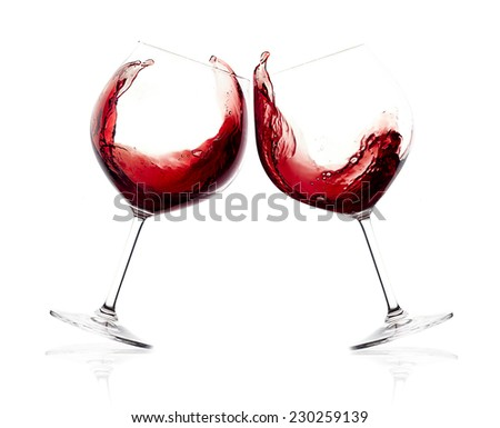 Cheers. A Toast with Red Wine. Splash. Two glasses clicking together over white background. Splashing red wine on balloon glasses - stock photo